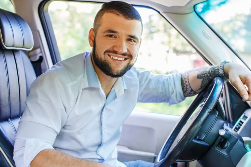 Happy male with black hair and beard, tattoes on his hand, dressed in white shirt and blue jeans shorts driving a car.